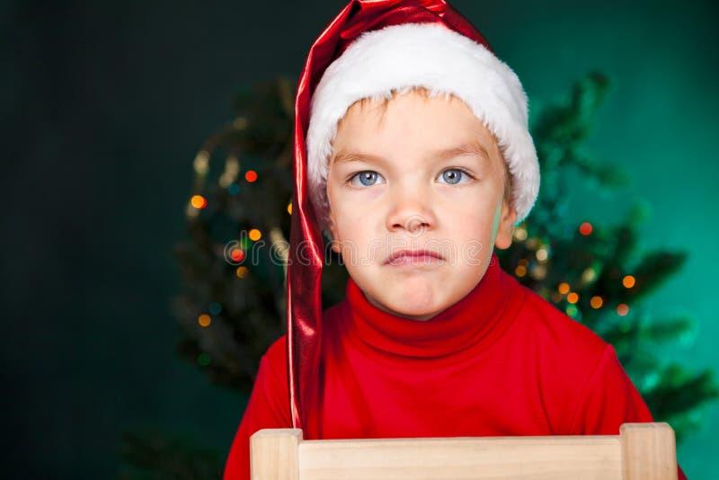 圣诞老人帽子的坏小的男孩 免版税库存照片