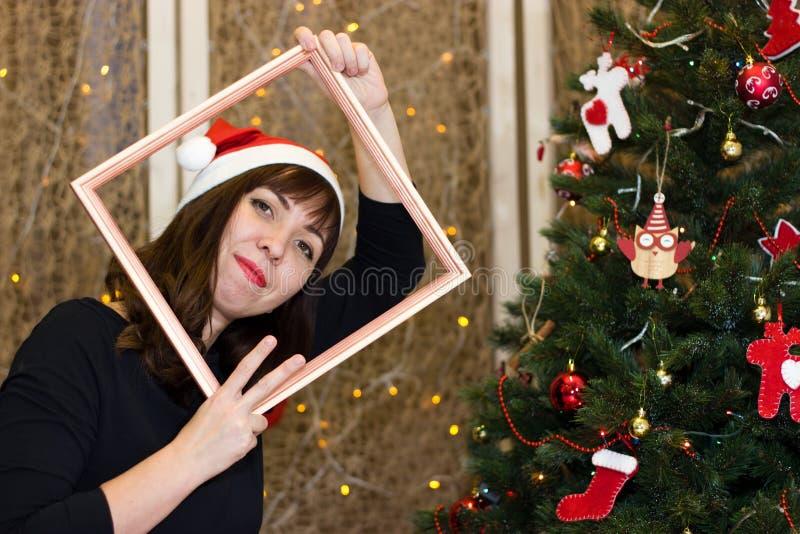 圣诞老人帽子的女孩在他的ha将保留框架 免版税库存图片