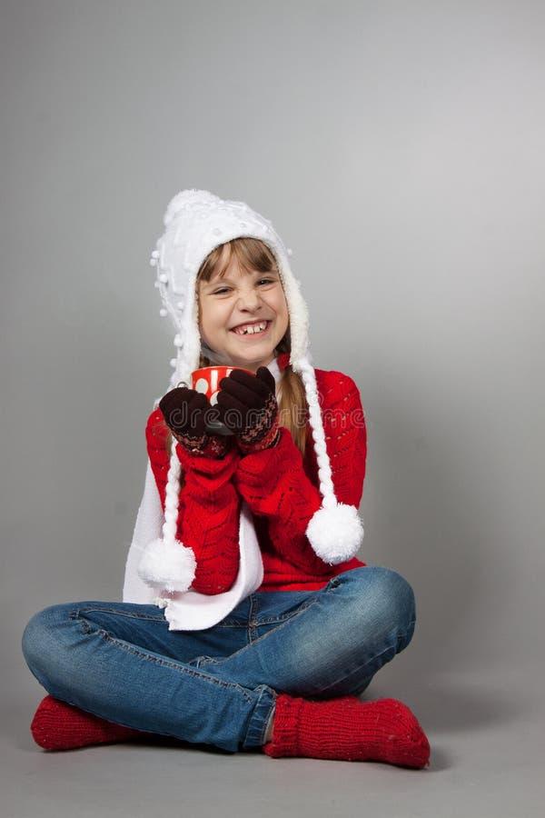 圣诞老人帽子的女孩有杯子的 免版税库存照片