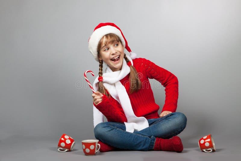 圣诞老人帽子的女孩有杯子的 库存照片