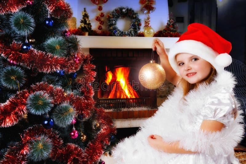 圣诞老人帽子的女孩装饰圣诞树的 库存图片