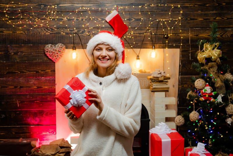 圣诞老人帽子的妇女在家 礼物情感 新年度 女孩新年度 有红色圣诞礼物箱子的妇女 新的妇女 免版税库存照片