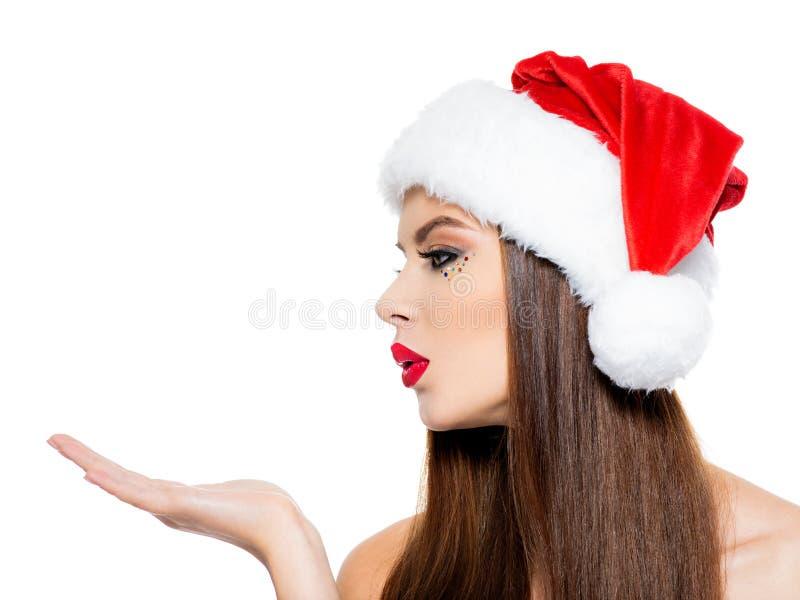 圣诞老人帽子的妇女送一个亲吻 与棕榈的美女的面孔在与在白色背景-隔绝的亲吻的标志的面孔附近 库存图片
