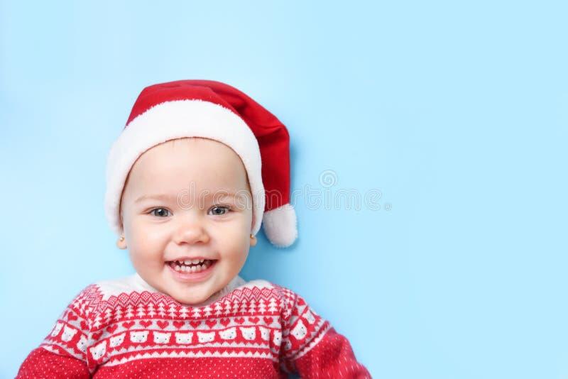 圣诞老人帽子的婴孩在蓝色空的空间背景 免版税库存图片