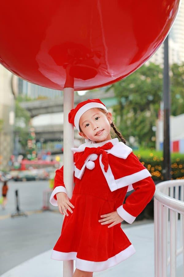 圣诞老人帽子的孩子女孩获得乐趣在圣诞节打过工 背景快活的xmas 免版税库存图片