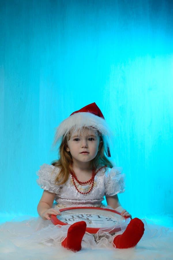 圣诞老人帽子的小女孩有时钟的 免版税库存照片