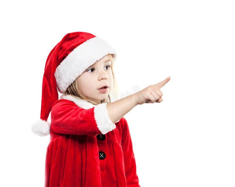 圣诞老人帽子的小婴孩 圣诞节孩子指向手指 库存图片