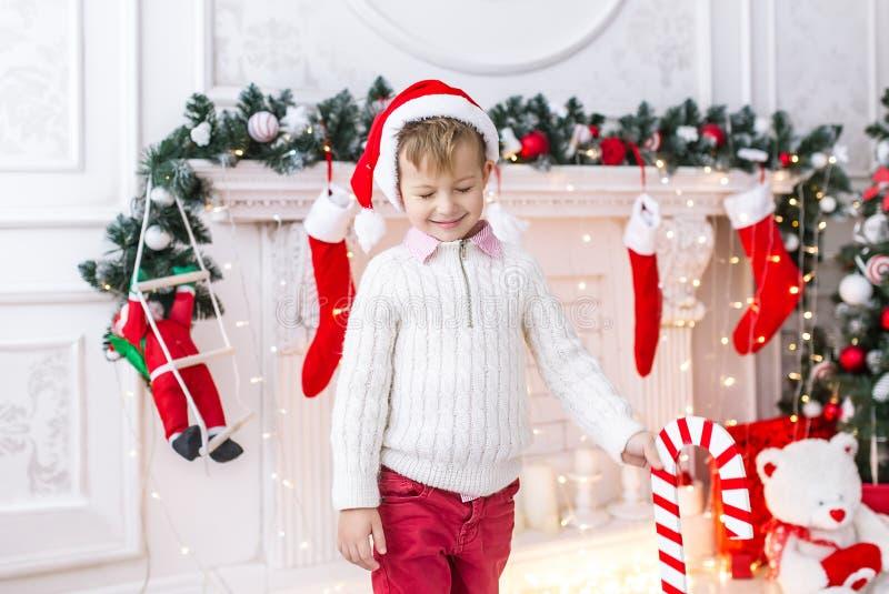 圣诞老人帽子的小男孩作白日梦支持她的头用手和闭合的眼睛 免版税图库摄影