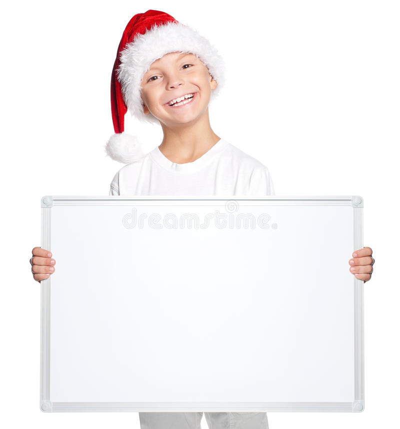 圣诞老人帽子的小男孩有空白的委员会的 库存照片