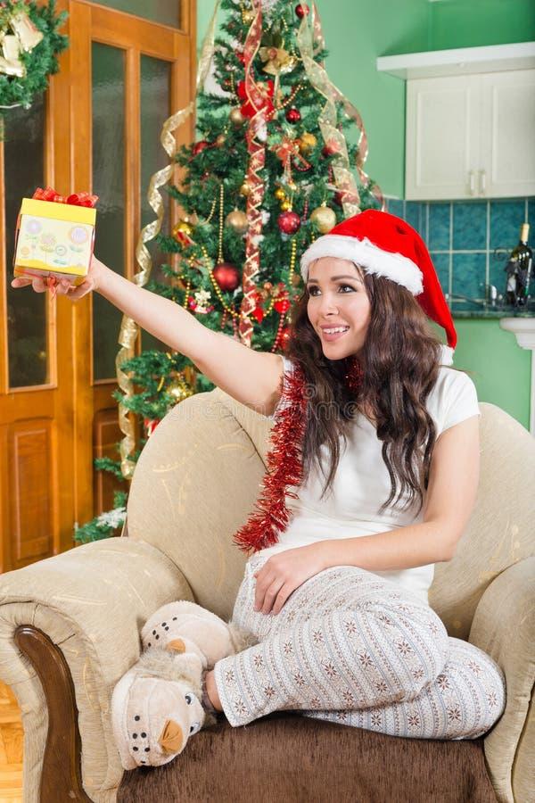 圣诞老人帽子的少妇提供有丝带的礼物盒 库存图片