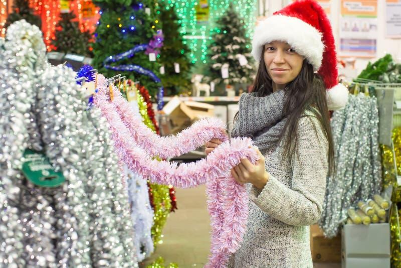 圣诞老人帽子的少妇选择装饰  图库摄影