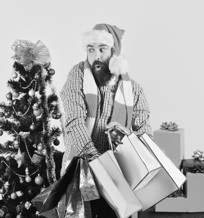 圣诞老人帽子的年轻人走与购物带来的 免版税库存图片