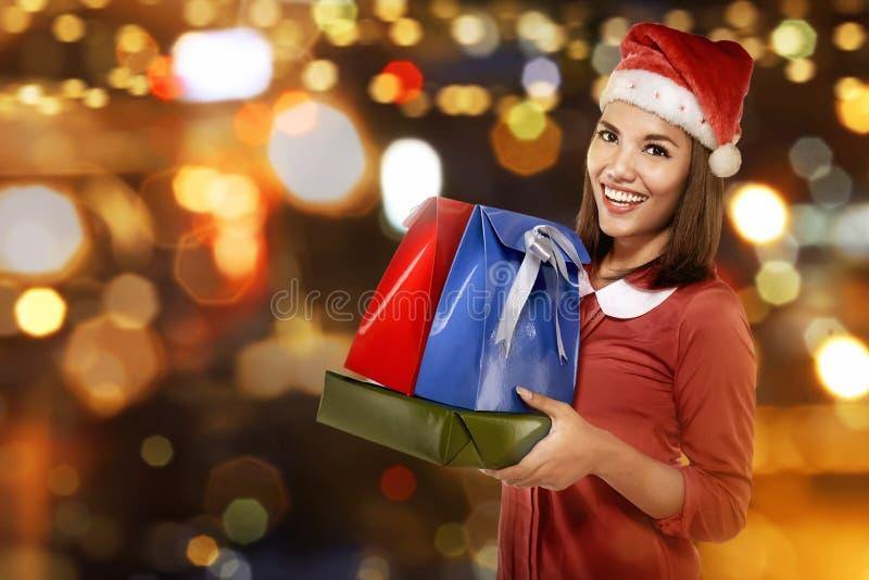 圣诞老人帽子的微笑的亚裔妇女有许多礼物盒的 免版税库存照片
