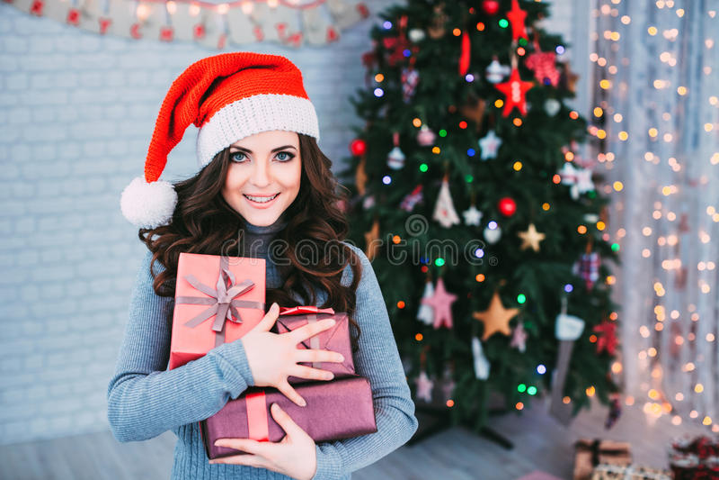 圣诞老人帽子的微笑的妇女有许多礼物盒的 图库摄影