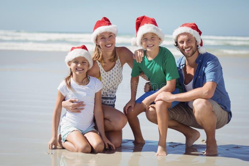 戴圣诞老人帽子的微笑的家庭画象在海滩 库存图片
