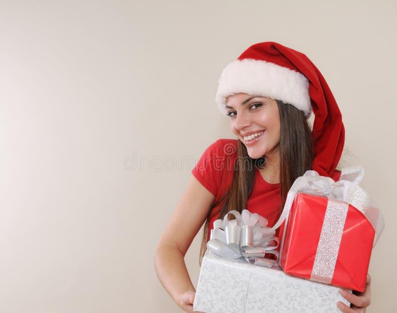 圣诞老人帽子的微笑的美丽的少妇有基督的礼物的 库存照片
