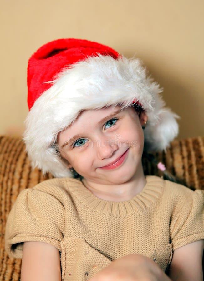 圣诞老人帽子的快乐的女孩 库存照片