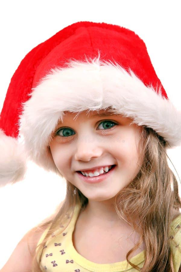 圣诞老人帽子的快乐的女孩 免版税库存照片