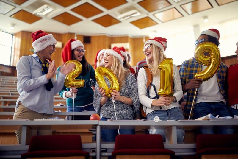 圣诞老人帽子的愉快的同事 获得乐趣在大学的新年庆祝 免版税库存照片