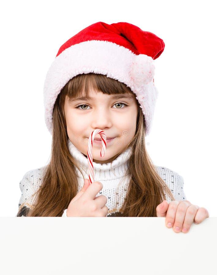 圣诞老人帽子的愉快的女孩有圣诞节棒棒糖常设behin的 库存照片