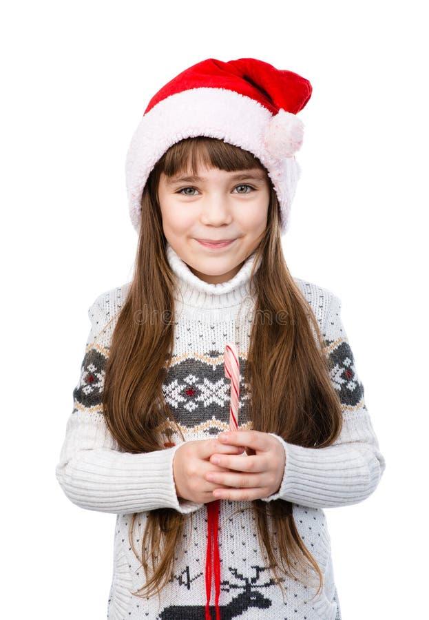 圣诞老人帽子的愉快的女孩有圣诞节棒棒糖的 查出在白色 免版税库存照片