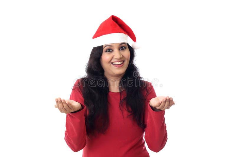 圣诞老人帽子的愉快的妇女有在开放手棕榈的空的拷贝空间的 免版税库存图片