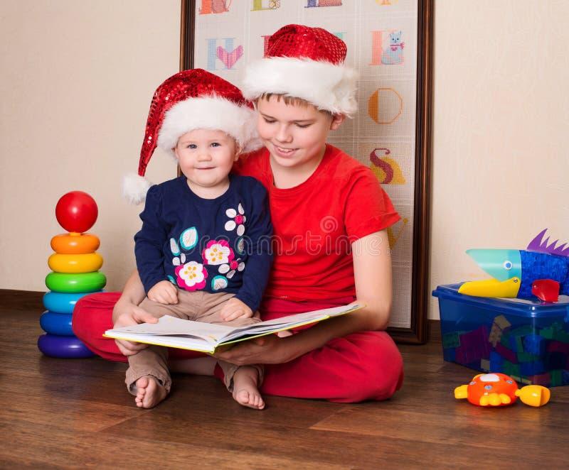 圣诞老人帽子的愉快的孩子读圣诞节书的 大汤 库存照片