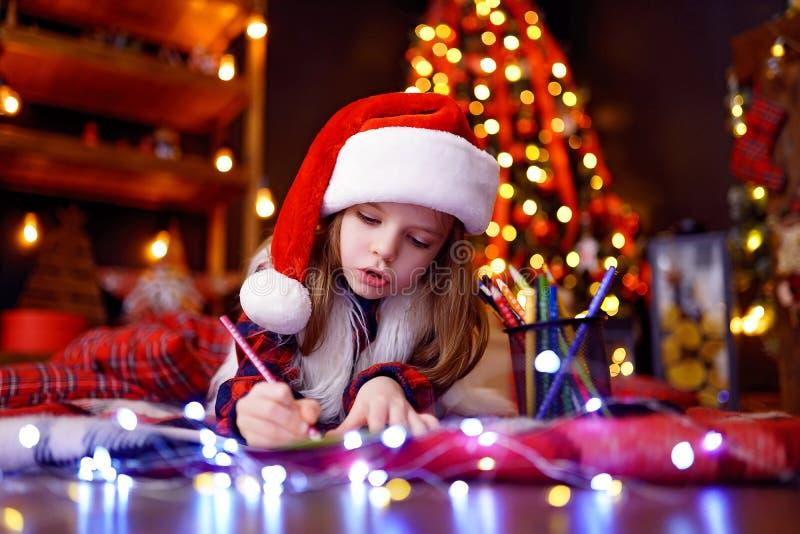 圣诞老人帽子的滑稽的女孩给圣诞老人写信 免版税库存照片