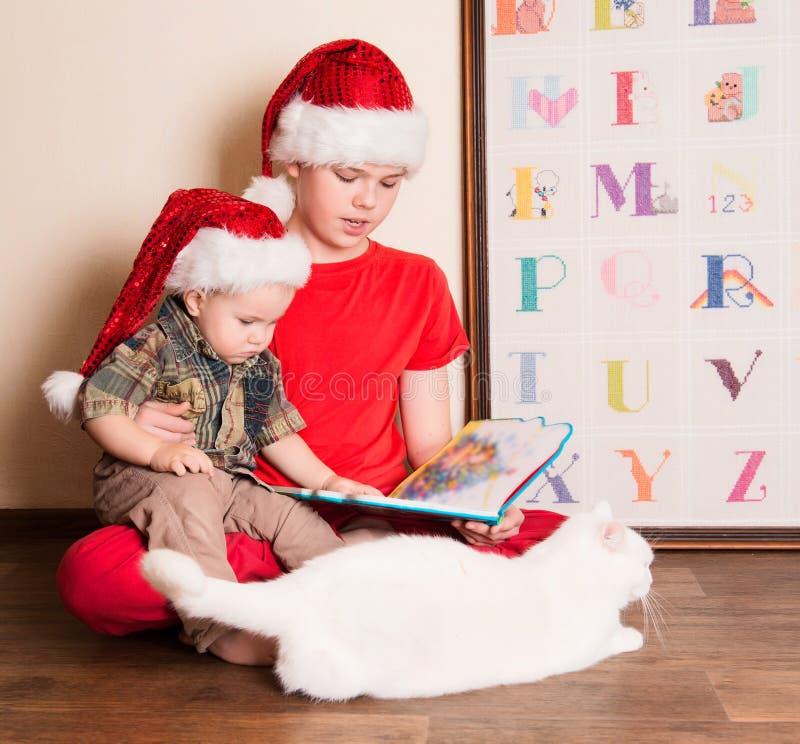 圣诞老人帽子的男孩读圣诞节书的 哥哥读书 免版税库存图片