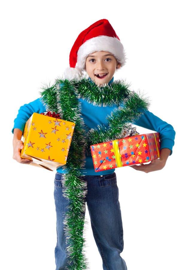 圣诞老人帽子的笑的女孩与礼物盒 图库摄影