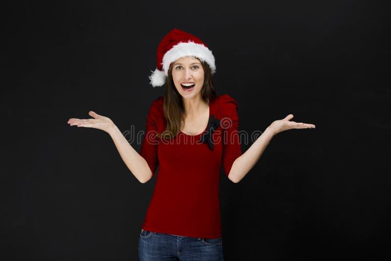 戴圣诞老人帽子的美丽的妇女 库存图片