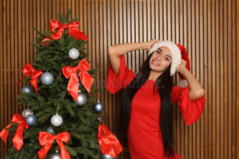 圣诞老人帽子的美丽的少妇在圣诞树附近 免版税库存照片