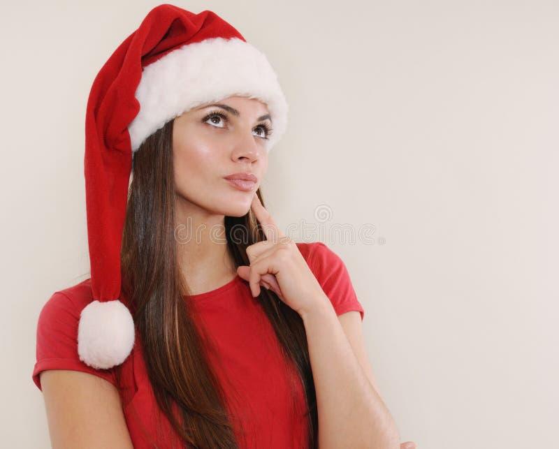 圣诞老人帽子的美丽的少妇考虑圣诞节礼物的 图库摄影