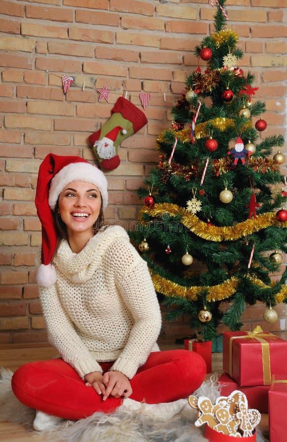 圣诞老人帽子的美丽的微笑的少妇圣诞节的在家 库存照片