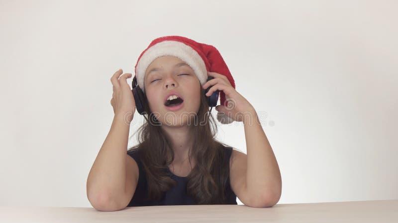 圣诞老人帽子的美丽的淘气女孩少年在白色背景听到在耳机的音乐并且唱歌  免版税图库摄影