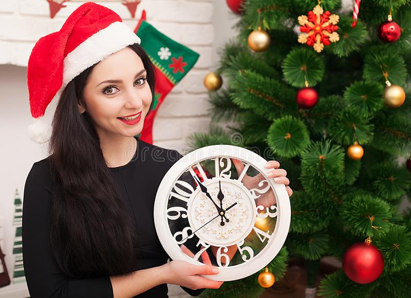 圣诞老人帽子的逗人喜爱的女孩有装饰的圣诞树和老时钟的 库存照片