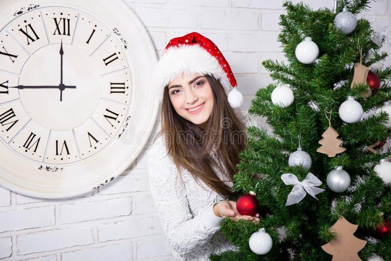 圣诞老人帽子的逗人喜爱的女孩有装饰的圣诞树的 库存照片