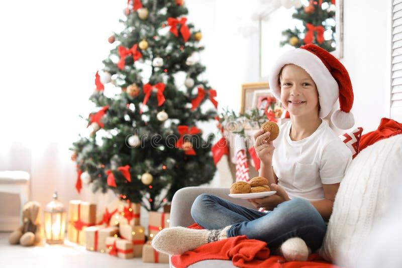 圣诞老人帽子的逗人喜爱的小孩吃圣诞节曲奇饼的 免版税库存照片