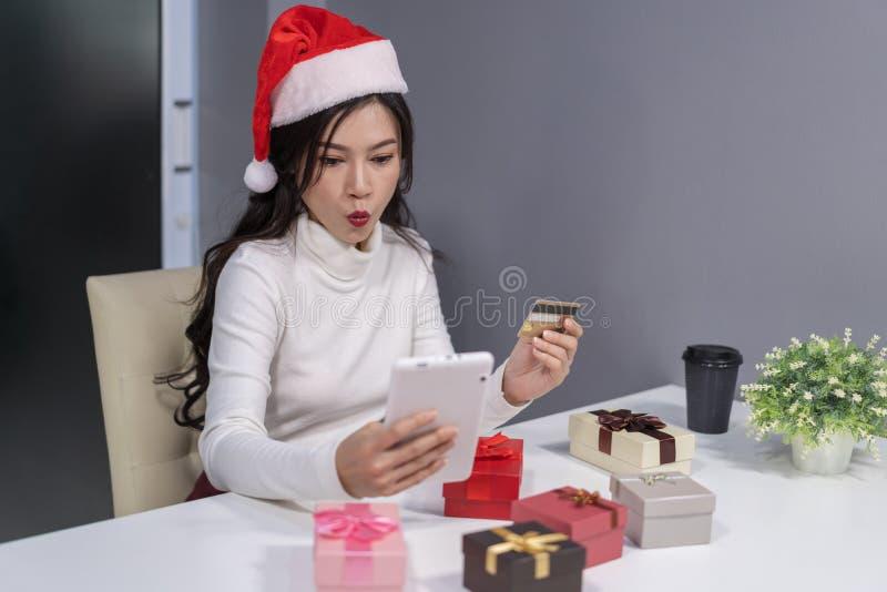 圣诞老人帽子购物的震惊妇女网上为圣诞礼物wi 库存图片