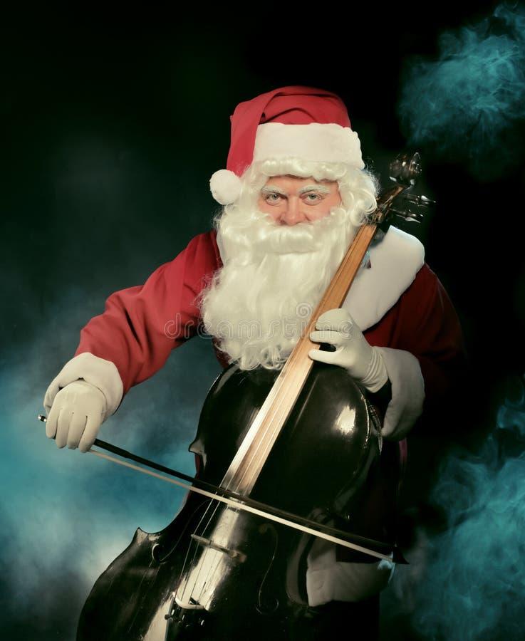 圣诞老人弹在黑暗的背景的Cklaus大提琴 库存图片