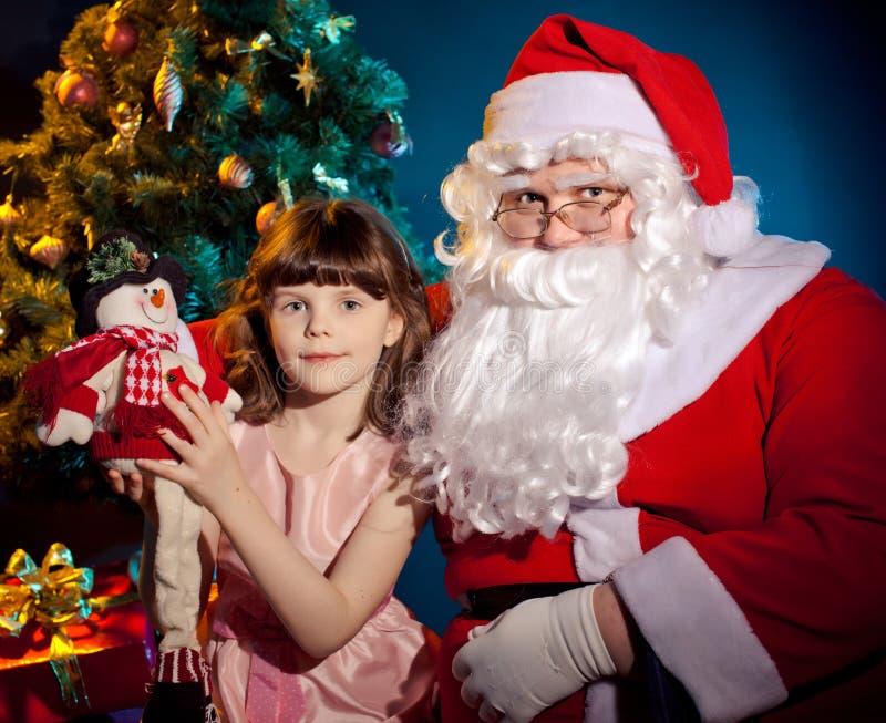 圣诞老人拿着袋子的和拿着玩具的小女孩 库存照片