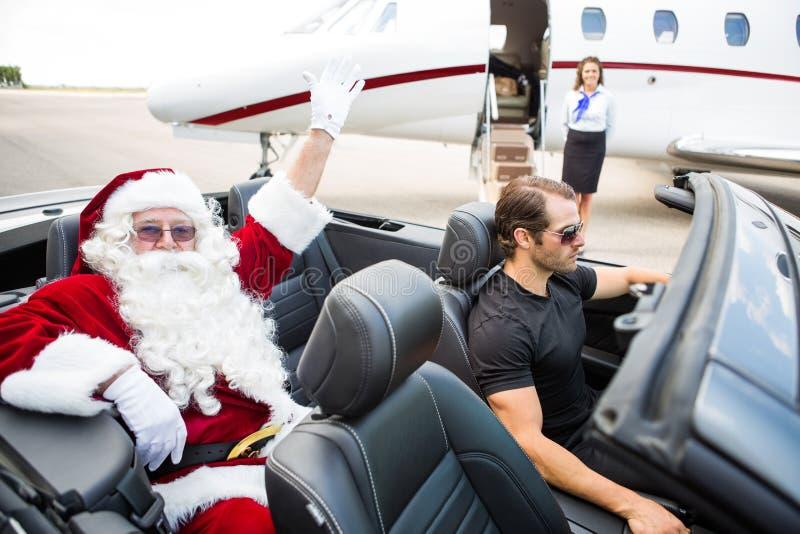 圣诞老人挥动的手,当汽车夫驾驶时 免版税库存照片