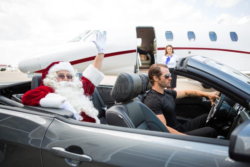 圣诞老人挥动的手,当驾驶敞篷车时的司机 免版税库存图片