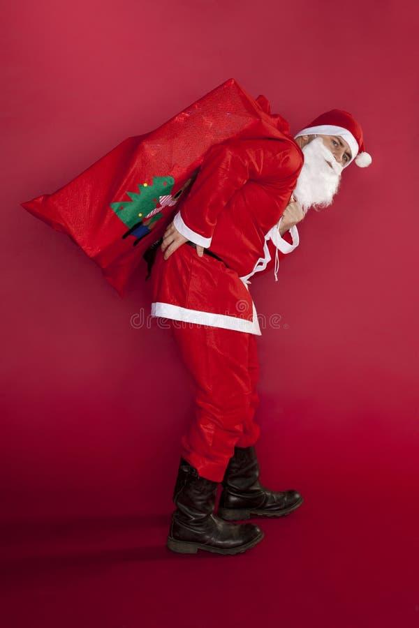 圣诞老人有从重量的背部疼痛礼物 库存照片