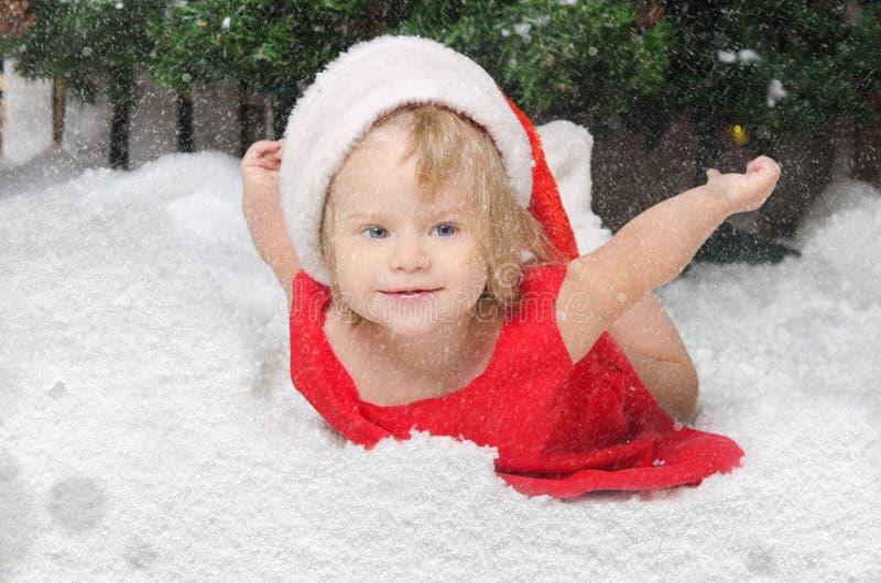圣诞老人服装的女孩在雪 图库摄影