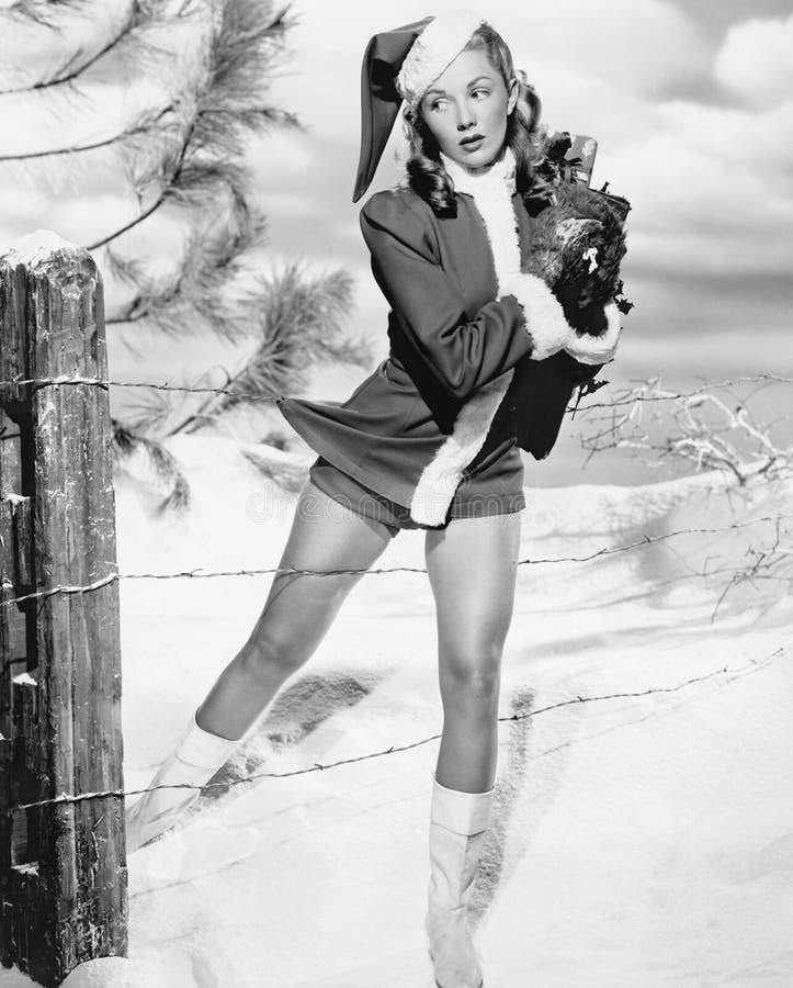 圣诞老人服装的妇女被逮住在铁丝网篱芭的(所有人被描述不更长生存,并且庄园不存在 免版税库存图片