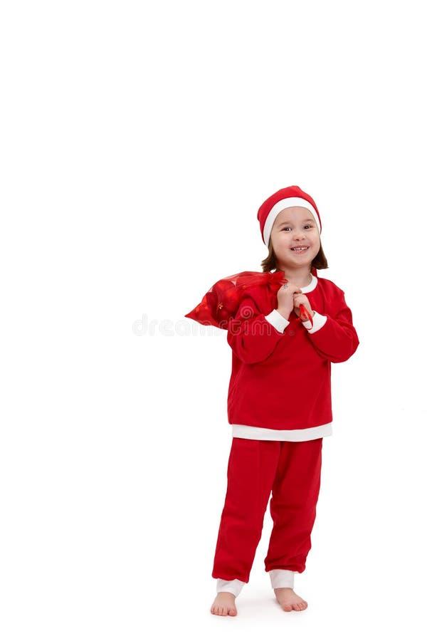 圣诞老人服装的小愉快的女孩 免版税库存照片