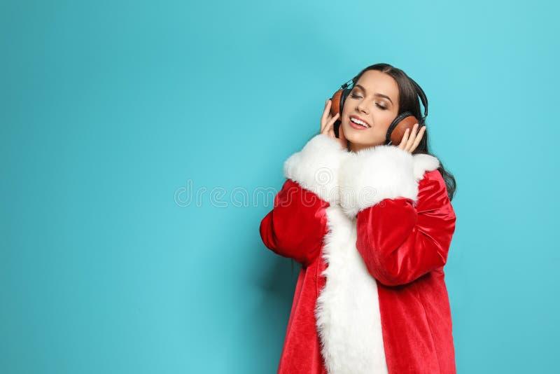 圣诞老人服装的少妇听到圣诞节音乐的 免版税库存照片