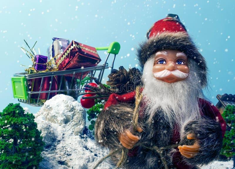 圣诞老人玩偶和购物车有圣诞节礼物的 免版税库存照片