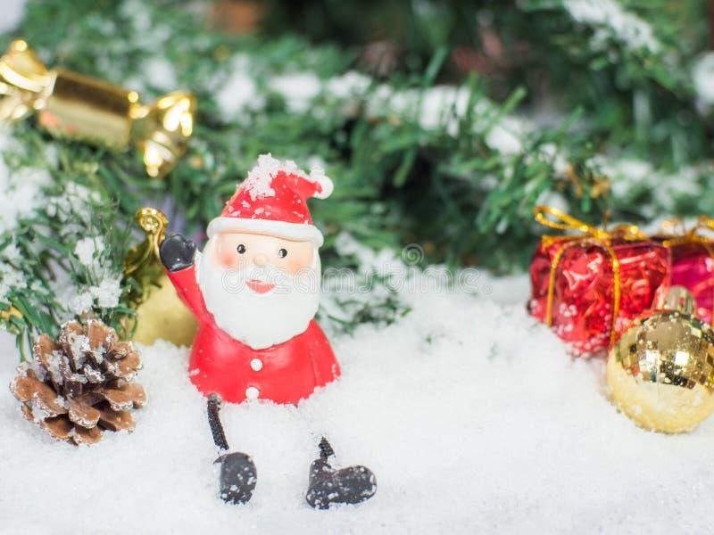 圣诞老人玩偶和glod圣诞节球和红色箱子在sno 库存图片
